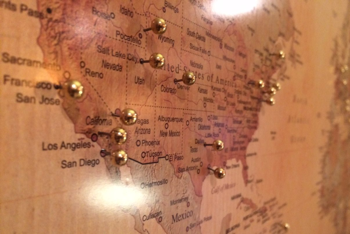 A map of the United States with gold pins in some cities.