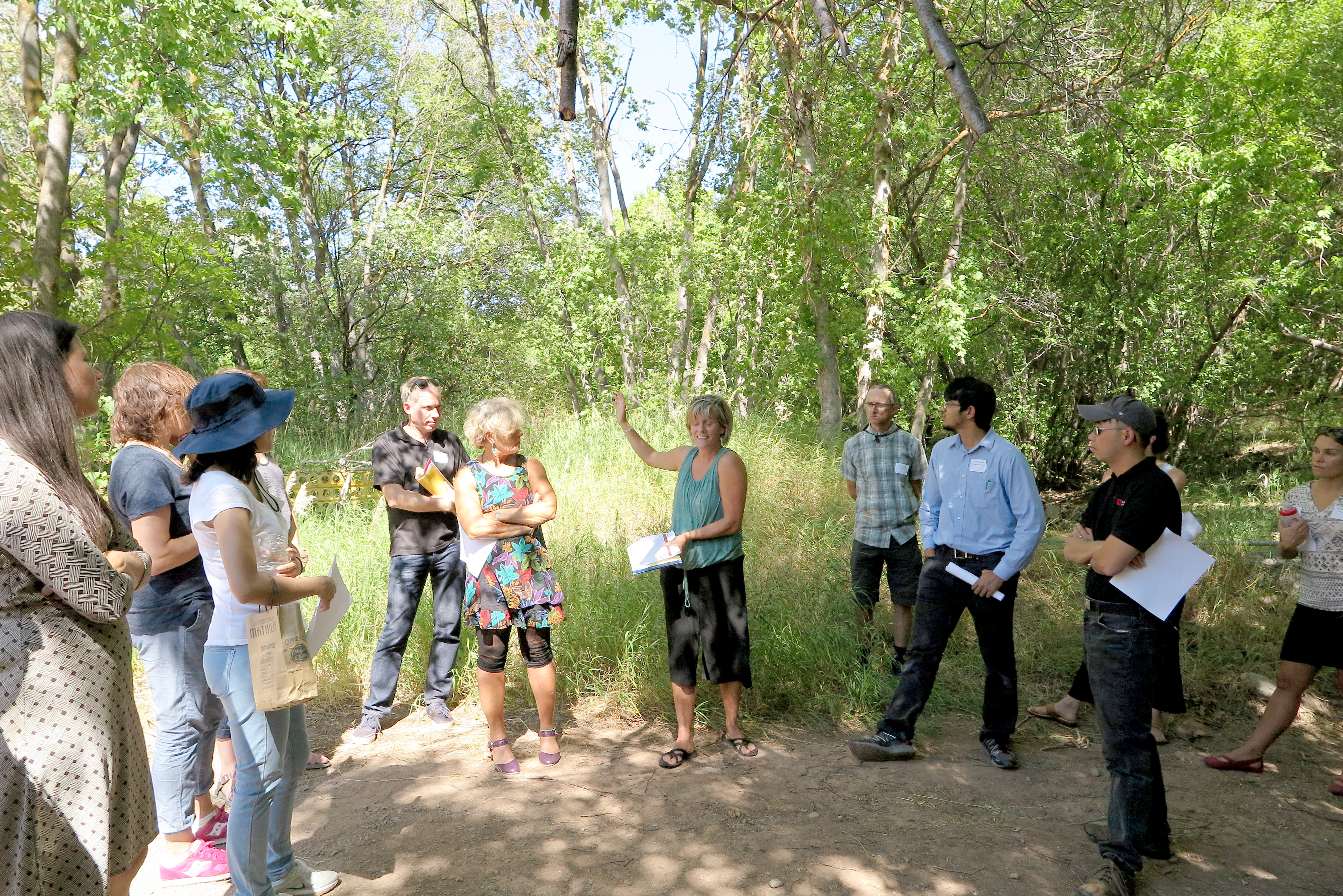 A group of University of Utah faculty standing in a circle discussing sustainability topics surrounded by greenery.