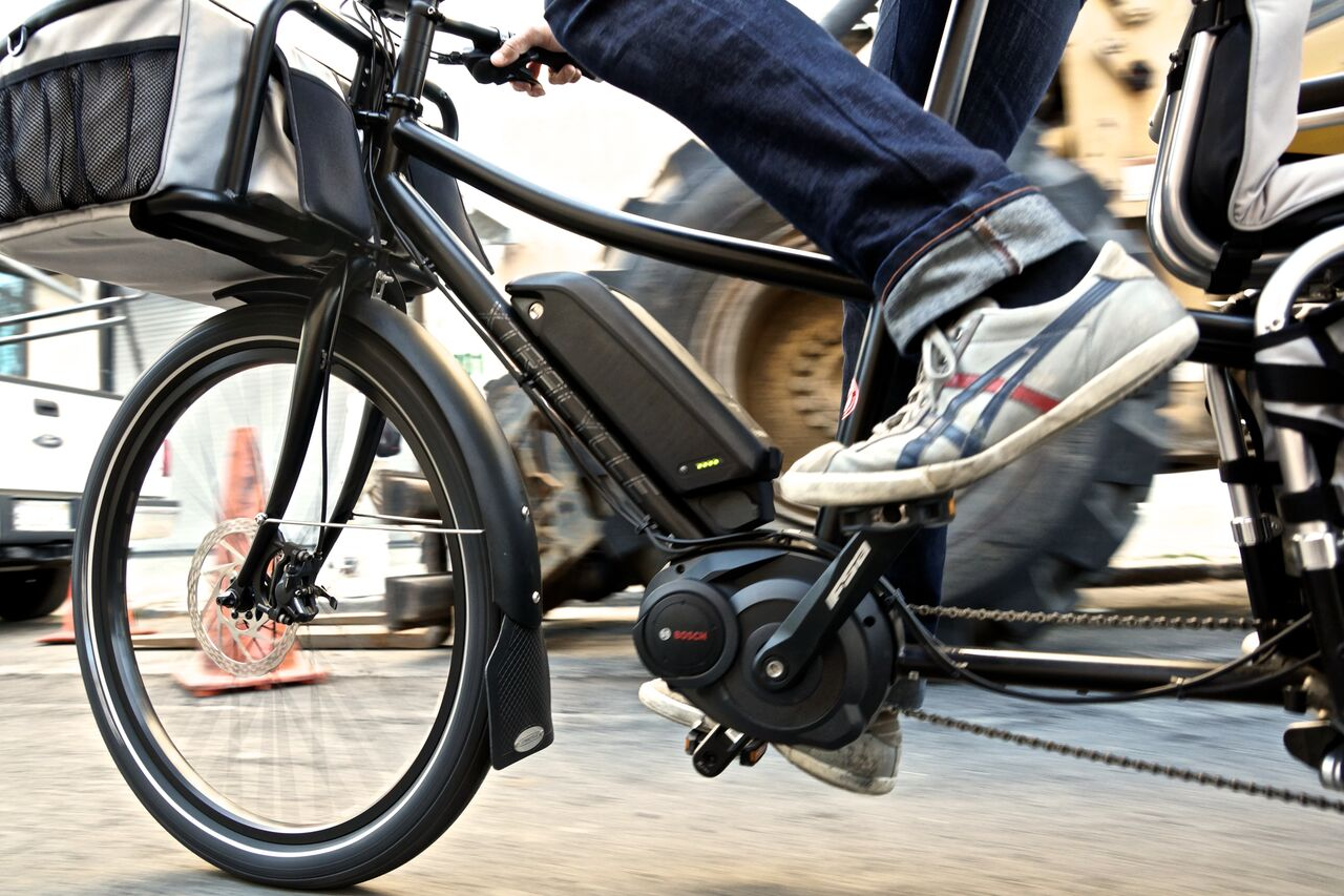 photo features the frame of an ebike with a rider in oldschool leather sneakers. A bag is affixed to the handlebars.