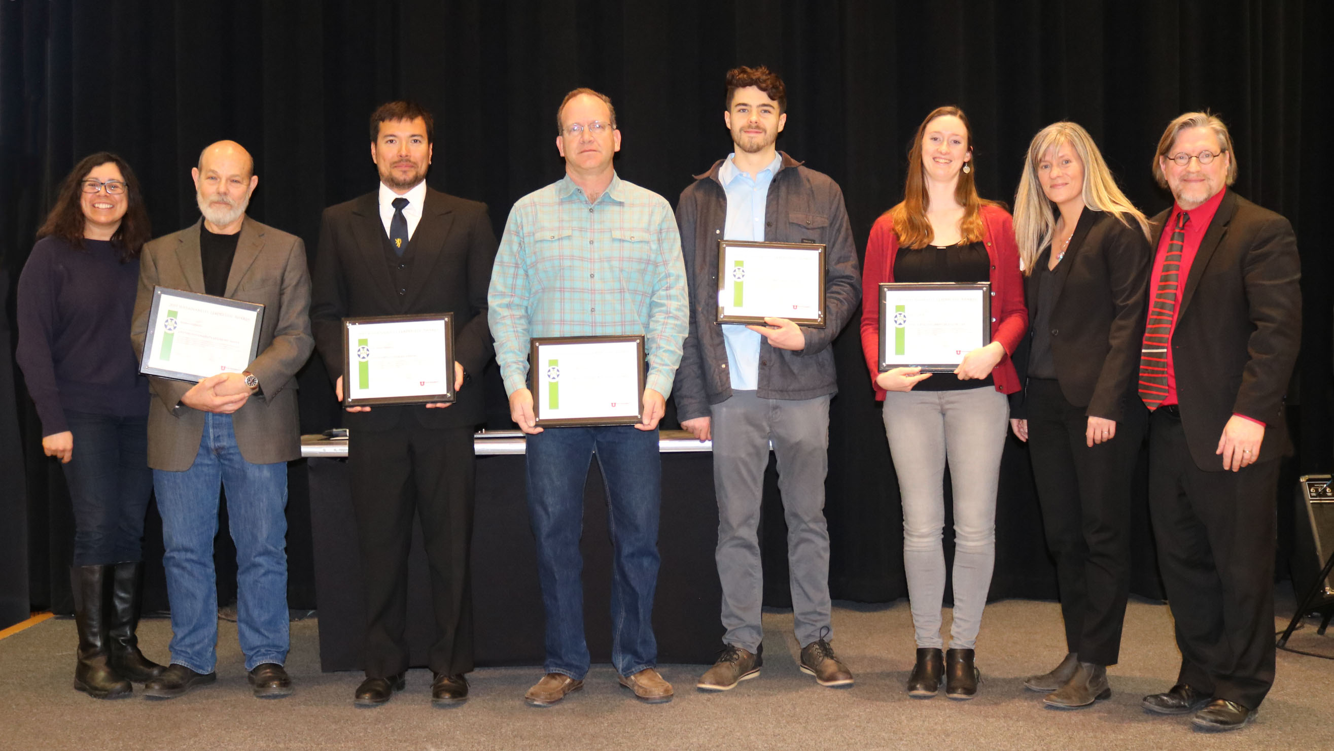 A group of 8 faculty, staff and students stand on a stage holding their Sustainability Leadership Award plaques.