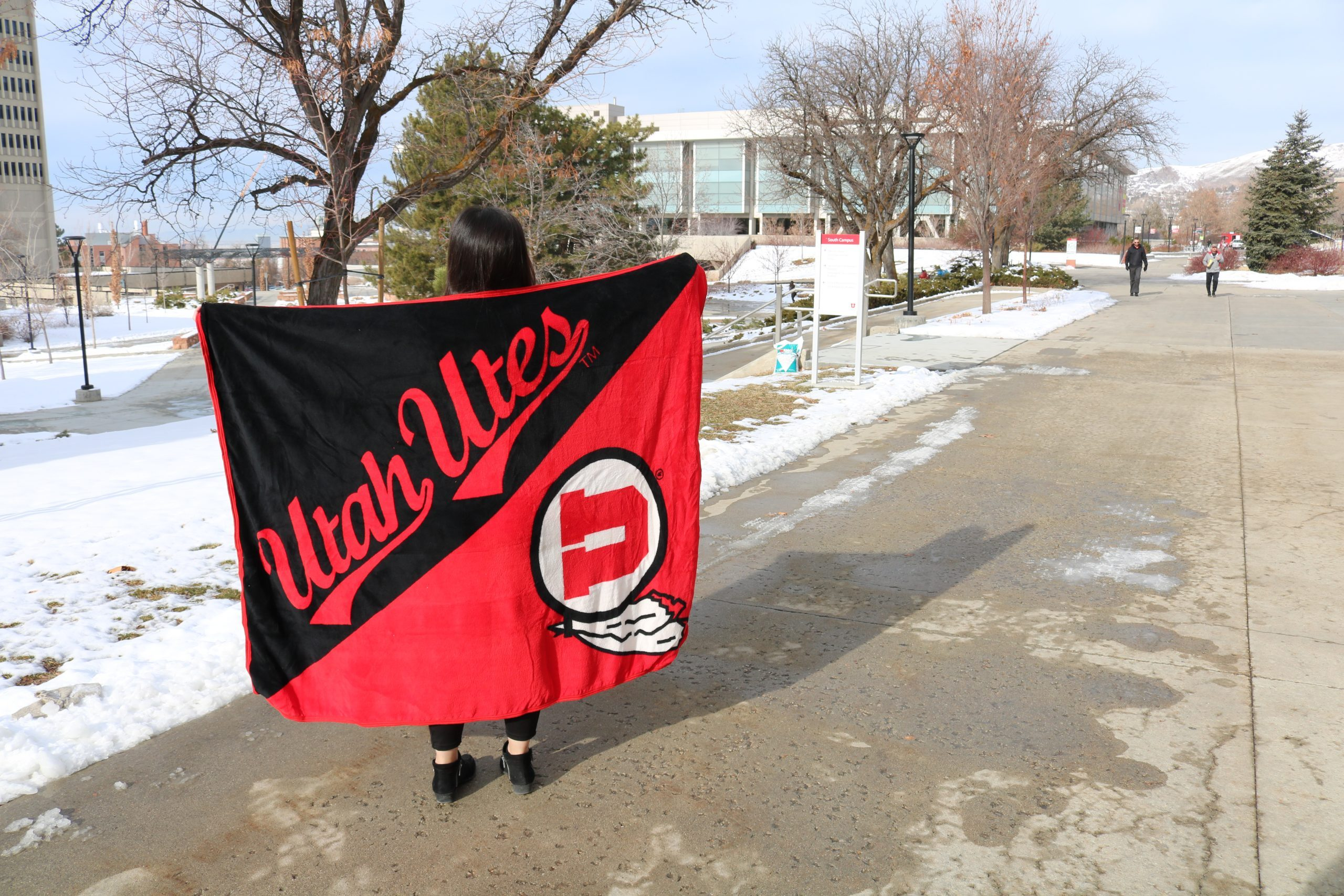 Student holds plush U-branded blanket on campus walkway