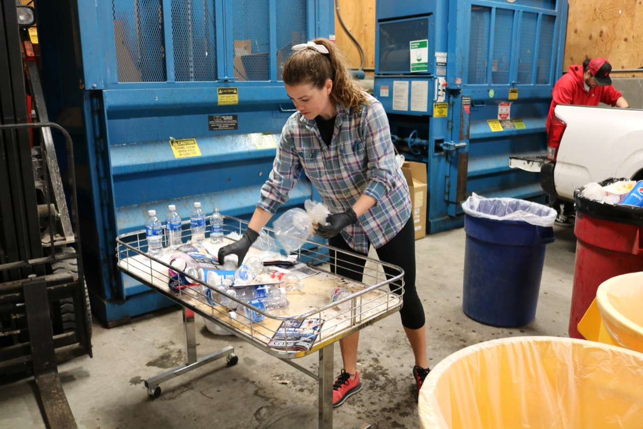 Abby Ghent sorts recycling from the March 6 Utah Red Rocks gymnastics meet.