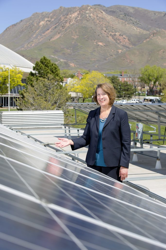 Ruth Watkins stands with campus solar panel.