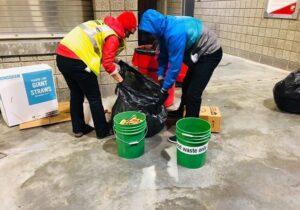 Two volunteers sort through food waste after an October 2019 University of Utah Football Game.