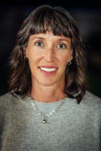 Headshot of Dr. Jennifer Watt wearing light gray sweater with silver necklace. Dr. Watt has bangs and shoulder-length wavy brown hair.