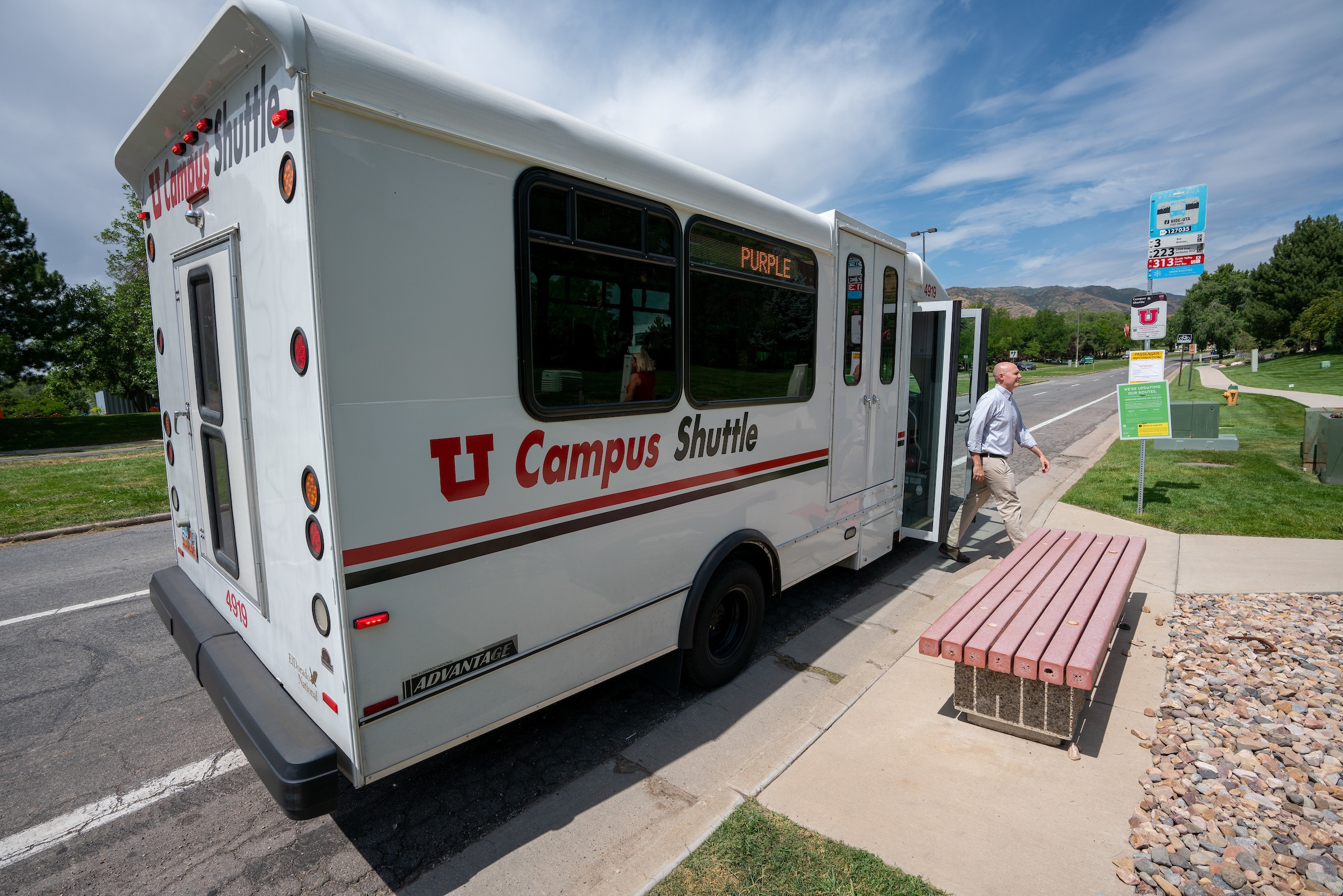A campus shuttle picks lets off a rider on a sunny, early summer day. Wispy clouds are in the sky.